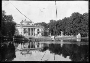 Popękany negatyw z czasów I wojny światowej. Przedstawia letni Pałac na Wyspie w Łazienkach. Widac jego południową fasadę, staw przed Pałacem oraz pokryte liścmi drzewa w parku, flankujące budynek i staw.