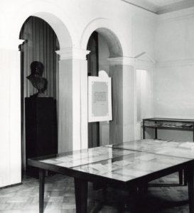 Sala II wystawy z 1958 roku poświęcona założycielom i założeniu Uniwersytetu, jego inauguracji i organizacji. Widać wnętrze obecnego magazynu bivlioteki Instytut Muzykologii. N a środku sali wielka gablota wyglądająca jak stół, a w niej, pod szkłem, mnóstwo dokumentów. Za gablotą przejście przez ścianę w kształcie dwóch łuków z filarem pośrodku, Przejście prowadzi do wnęki, w której stoi popiersie Stanisława Staszica.