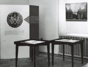 Fragment wystawy o historii Uniwersytetu z 1958 roku poświęcony uczelni w latach 1915-1918. Widać wnętrze z dwiema płaskimi gablotami przypoinajacymi stoły, połączonymi rogami. Za nim, nieco na lewo, stoi ścianka z planszą. Na planszy widać odbitkę dużej pieczęci uniwersyteckiej. Na prawo widać ścianę z kaloryferem, nad którym wisi zdjęcie przedstawiające Bramę Główną Uniwersytetu..