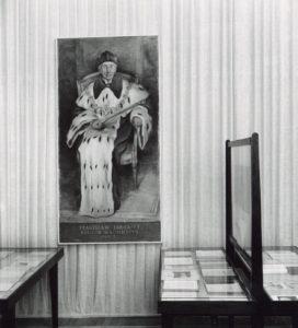 Na zdjęciu widać salę XII wystawy o historii Uniwersytetu Warszawskiej z 1958 roku, poświęconą Wydziałowi Matematyczno-Fizycznemu w latach 1915-1939. W Sali stoją trzy gabloty z papierami. Nad nimi wisi postret rektora Stanisława Thuguta w oficjalnym stroju rektorskim, czyli todze, birecie z łańcuchem na szyi. W prawej ręce rektor trzyma długie berło, a na nosie ma duże, okragłe okulary.