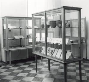Na zdjęciu widać fragment wystawy z 1958 roku poświęconej historii Unwiersytetu Warszawskiego. Jest to części poświęcona archeologii polskiej i śródziemnomorskiej.Są tu dwie gabloty z dokumentami glinianymi naczyniami.