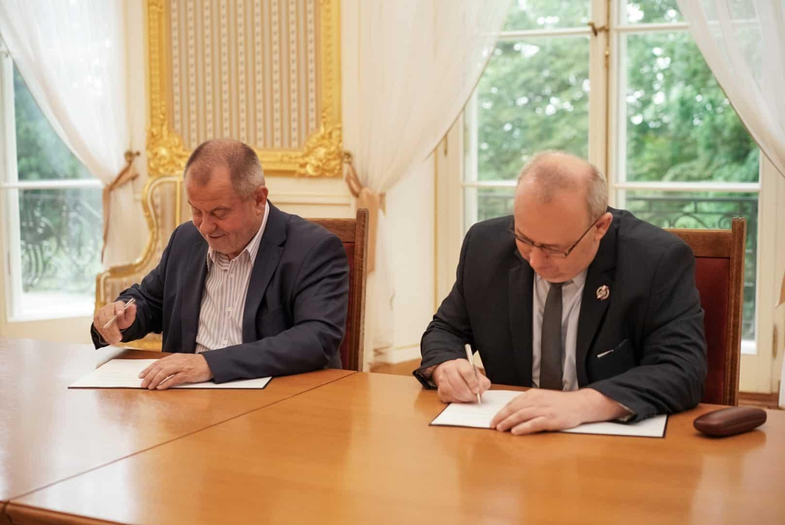 Rektor Uniwersytetu Warszawaskiego i dyrektor Muzeum Wojska Polskiego, ubrani w garnitury, podpisują porozumienie, każdy swój egzemplarz. W wielkiej, złoconej sali