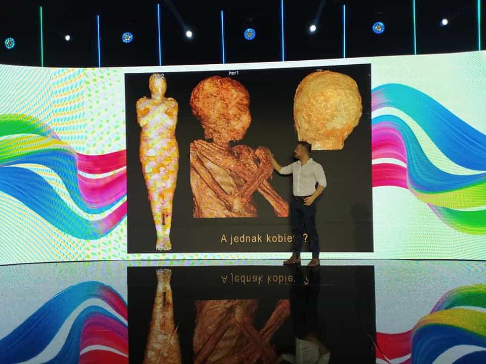 Scena konferencji organizowanej przez General Electric. NA scenie stoi pan Wojciech Ejsmond i omawia zdjęcia płodu znalezionego we wnętrzu egipskiej mumii ze zbiorów Muzeum Uniwersytetu Warszawskiego.