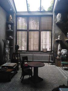 Wnętrze pracowni Karola tchorka i Katy Bentall. Widać rozległe studio z wielkim oknem i szyberdachem, ze ścianami zajętymi przez półki z rzeźbami Karola Tchorka. Na środku wnętrza stoją stół i krzesło, a pod ściana po lewej stronie stół roboczy, na którym leżą szkice.