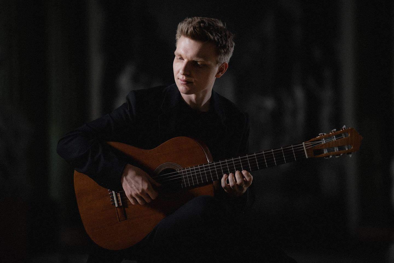 Mateusz Kowalski, blondyn około 30, ubrany w ciemne koszulę i marynarkę, siedzi z twarzą skierowana lekko w prawo. Trzyma na kolanach gitarę.